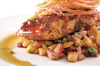 Emeril's barbecued salmon over andouille-potato hash with crispy fried onions.